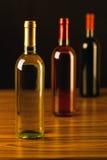 Três garrafas de vinho na tabela de madeira e no fundo preto Fotografia de Stock Royalty Free