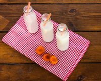 Três garrafas do leite no abricó da tabela Fotos de Stock Royalty Free