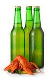 Três garrafas e as lagostas de cerveja clara empilham isolado no branco Fotografia de Stock Royalty Free