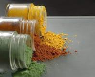 Três garrafas pequenas enchidas com os pós coloridos Fotografia de Stock