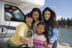Três-gerações de mulheres que fotografam autos fora do rv no lago Fotos de Stock Royalty Free