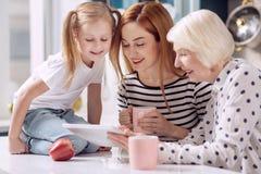 Três gerações de mulheres que olham o vídeo na tabuleta Fotos de Stock