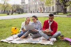 Três graduados que apreciam seu tempo de lazer fora imagem de stock