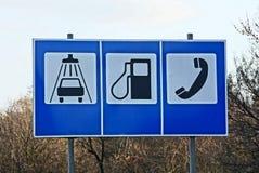 Três grandes sinais de estrada com informação sobre o serviço na rua perto da estrada Fotos de Stock Royalty Free