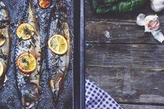 Três grelharam peixes, na bandeja preta do cozimento, com espaço da cópia Imagens de Stock