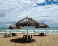 Três guarda-chuvas da palha e vadios da praia em um Sandy Beach bonito Imagens de Stock