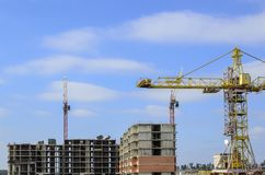 Três guindastes de construção no canteiro de obras Imagens de Stock
