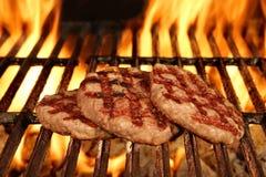 Três hamburgueres bronzeados caseiros na grade flamejante quente do BBQ Imagens de Stock