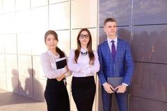 Três homem de negócios novo educado atrativo novo que sorri, holdi fotografia de stock