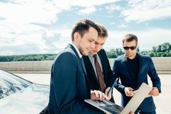 Três homem de negócios Using Digital Tablet fora contra o carro fotos de stock