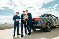 Três homem de negócios Using Digital Tablet fora contra o carro fotografia de stock