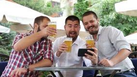 Três homens com as barbas que sentam-se no café, cerveja bebendo vídeos de arquivo