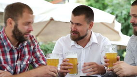 Três homens com as barbas que sentam-se no café com cerveja e que fazem a foto video estoque