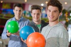 Três homens com bolas de boliches Imagem de Stock Royalty Free