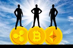 Três homens de negócios estão estando em três moedas da moeda cripto Foto de Stock