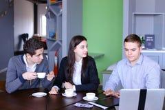 Três homens de negócios, mulher e homens discutindo o robô com o copo do te Imagem de Stock Royalty Free