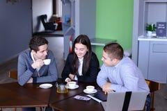 Três homens de negócios, mulher e homens discutindo o robô com o copo do te Fotos de Stock