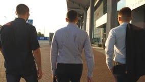 Três homens de negócios novos que andam na cidade Homens de negócio que comutam para trabalhar junto Indivíduos seguros que estão vídeos de arquivo