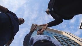 Três homens de negócios novos que encontram-se e para cumprimentar-se perto do prédio de escritórios Colegas masculinos que agita vídeos de arquivo