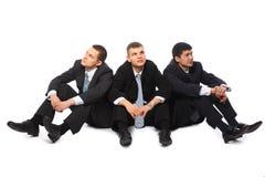 Três homens de negócios novos sentam-se no assoalho Imagem de Stock Royalty Free