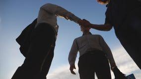 Três homens de negócios que encontram e que cumprimentam-se no ambiente urbano Os colegas agitam as mãos com o céu azul na cidade vídeos de arquivo
