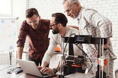 Três homens estão trabalhando em preparar uma impressora 3d para imprimir Um deles explica o resto da sutileza a cópia Fotografia de Stock Royalty Free