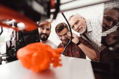 Três homens estão trabalhando para preparar o modelo impresso no modelo 3d do coração São satisfeitos com o resultado Foto de Stock Royalty Free