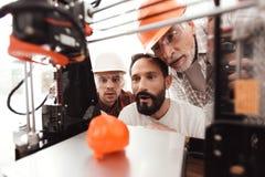 Três homens estão trabalhando para preparar o modelo impresso no modelo 3d do coração São satisfeitos com o resultado Fotografia de Stock Royalty Free
