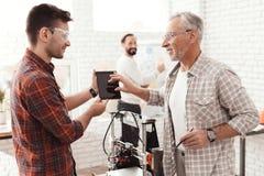 Três homens estabelecem uma impressora 3d feito a si próprio para imprimir o formulário Estão verificando o modelo 3d da tabuleta Fotografia de Stock Royalty Free