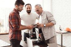 Três homens estabelecem uma impressora 3d feito a si próprio para imprimir o formulário Estão verificando o modelo 3d da tabuleta Imagens de Stock