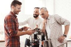 Três homens estabelecem uma impressora 3d feito a si próprio para imprimir o formulário Estão verificando o modelo 3d da tabuleta Imagem de Stock