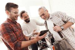 Três homens estabelecem uma impressora 3d feito a si próprio para imprimir o formulário Estão verificando o modelo 3d da tabuleta Imagens de Stock Royalty Free