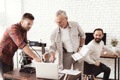 Três homens estabelecem uma impressora 3d feito a si próprio para imprimir o formulário Verificam o modelo 3d no portátil Fotografia de Stock Royalty Free
