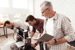 Três homens estabelecem uma impressora 3d feito a si próprio para imprimir o workpiece Um homem idoso com um caderno que olha seu Fotografia de Stock