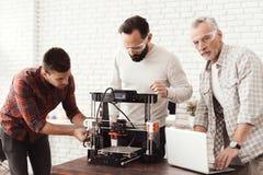 Três homens estabelecem uma impressora 3d feito a si próprio para imprimir o workpiece Um homem idoso com um portátil está olhand Fotos de Stock Royalty Free