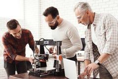 Três homens estabelecem uma impressora 3d feito a si próprio para imprimir o workpiece Um homem idoso com um portátil está olhand Foto de Stock