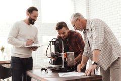 Três homens estabelecem uma impressora 3d feito a si próprio Um dos homens verifica a exatidão da configuração de dispositivo Fotos de Stock Royalty Free
