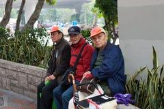 Três homens idosos têm um resto no parque imagens de stock royalty free