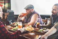 Três homens maduros que bebem a cerveja pilsen no bar Fotos de Stock