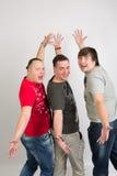 Três homens nos t-shirt e nas calças de brim Foto de Stock