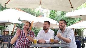 Três homens novos com fósforo de esporte de observação da cerveja no café vídeos de arquivo