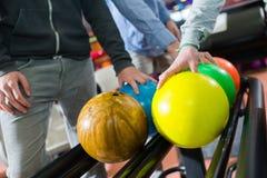 Três homens que escolhem suas bolas de boliches Imagem de Stock Royalty Free