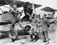 Três homens que estão ao lado de um avião que tem uma conversação (todas as pessoas descritas não são umas vivas mais longo e nen fotografia de stock royalty free
