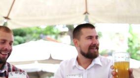 Três homens que sentam-se na tabela na frente dos vidros da cerveja e do t vídeos de arquivo