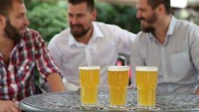 Três homens que sentam-se no café fora que olha o fósforo e que olha a VE video estoque