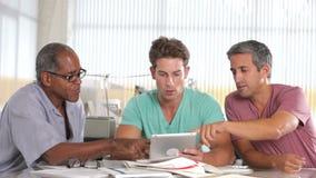 Três homens que usam o tablet pc no escritório criativo