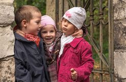 Três irmãos, crianças pequenas na porta velha no outono estacionam foto de stock