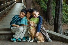 Três irmãos e seu cachorrinho Foto de Stock Royalty Free