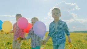 Três irmãos mais novo com balões da cor que andam no campo de florescência em férias de verão Fotos de Stock