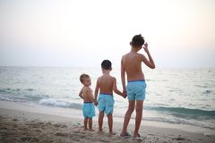 Três irmãos na praia, vista da parte traseira imagem de stock royalty free